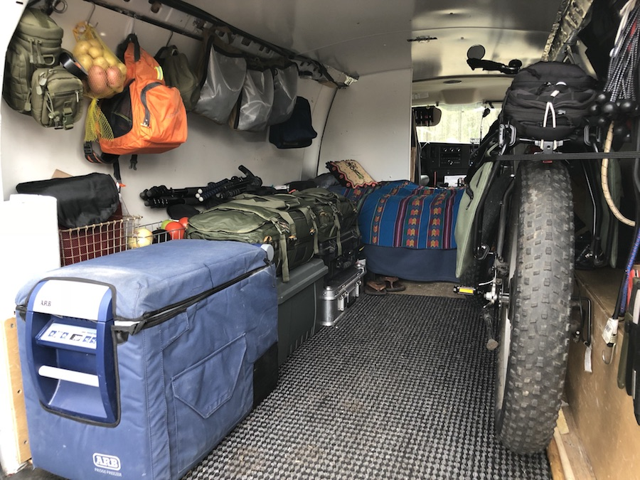 van interior with fridge/freezer, ebike, bed, and hanging gear