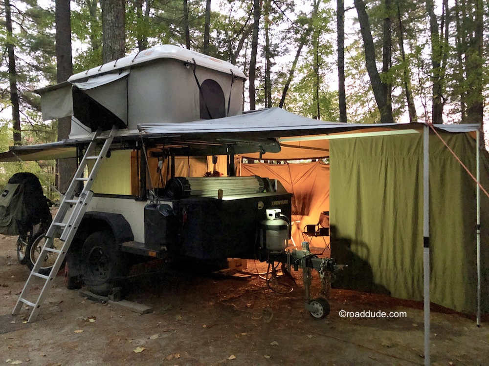 Adventure trailer set up for cold weather camping with awning, sidewalls, and rooftop tent