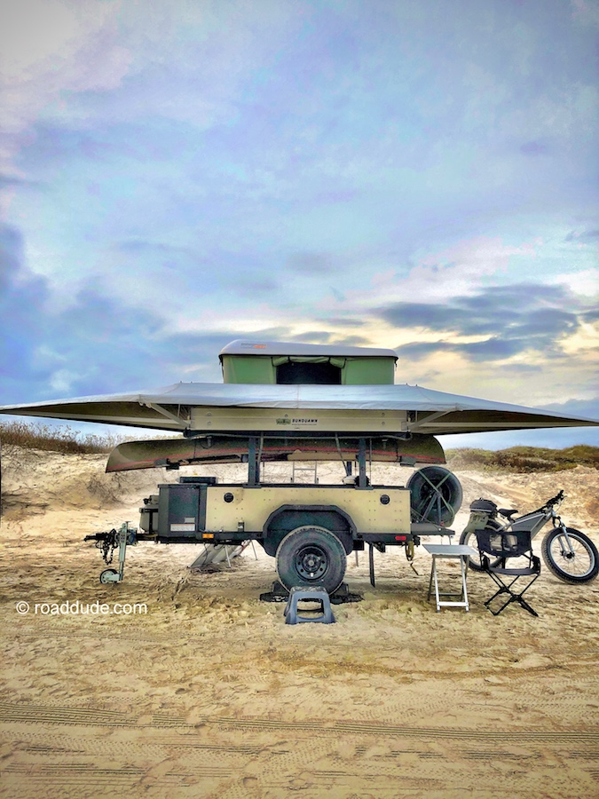 off-road trailer with awning and rooftop tent in beach setting with ebike nearby