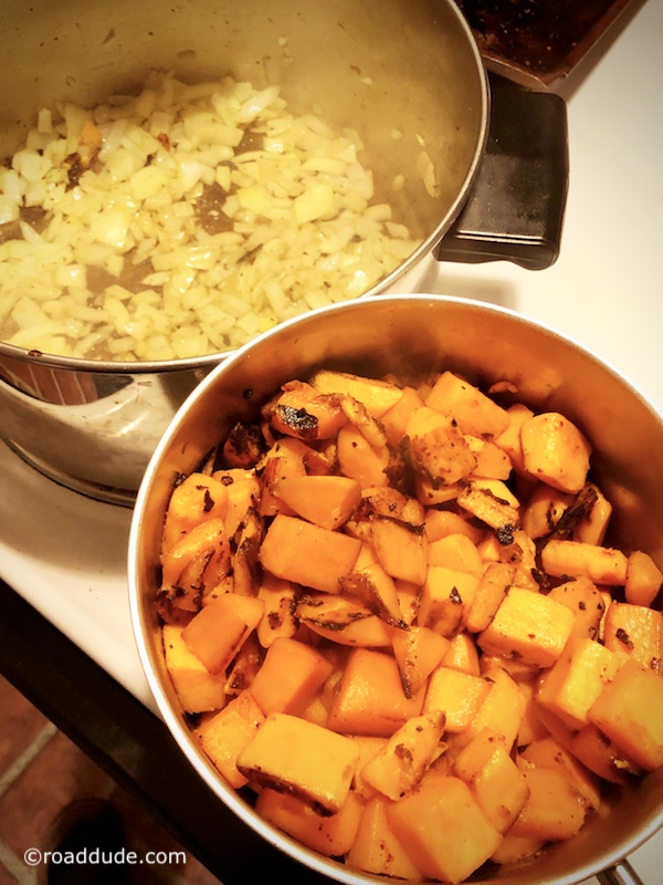 Onions cooking while heated sweet potatoes set aside