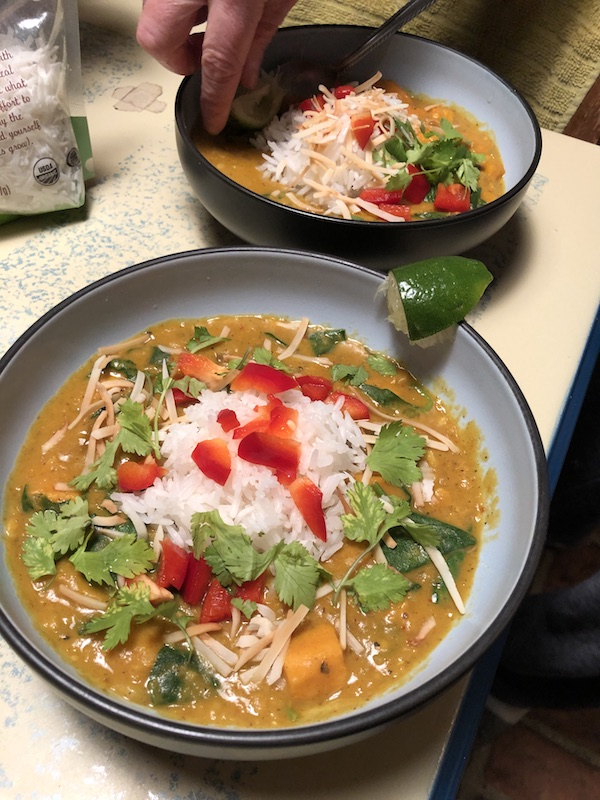 Two bowls Red Curry Lentils with Sweet Potatoes and Spinach with cilantro and red pepper garnish
