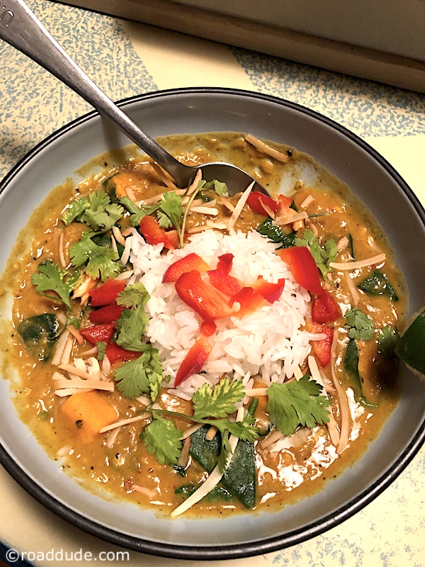 Red Curry Lentils with Sweet Potatoes and Spinach on rice in a bowl with red pepper and cilantro garnish