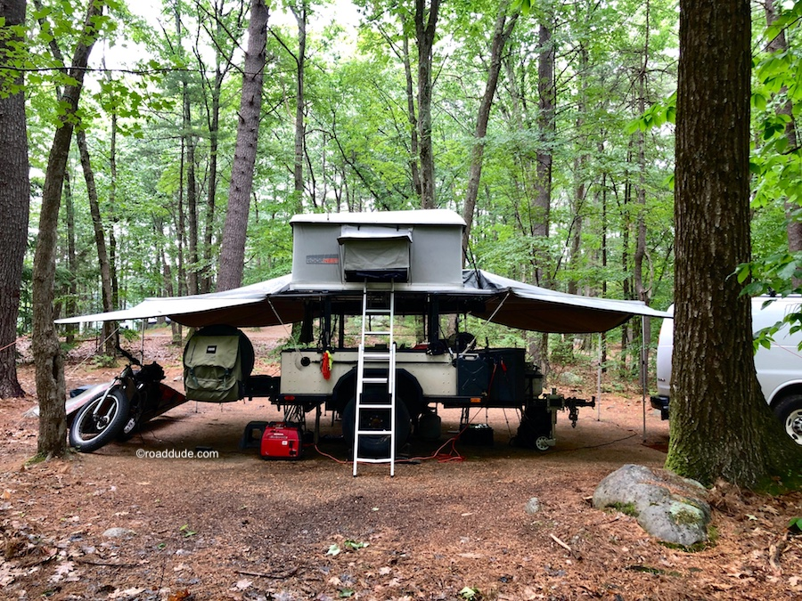 Basecamp with off-road trailer, rooftop tent, and expansive awning set up in the woods.