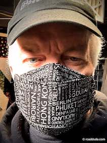 Man wearing facemasks with names of world cities